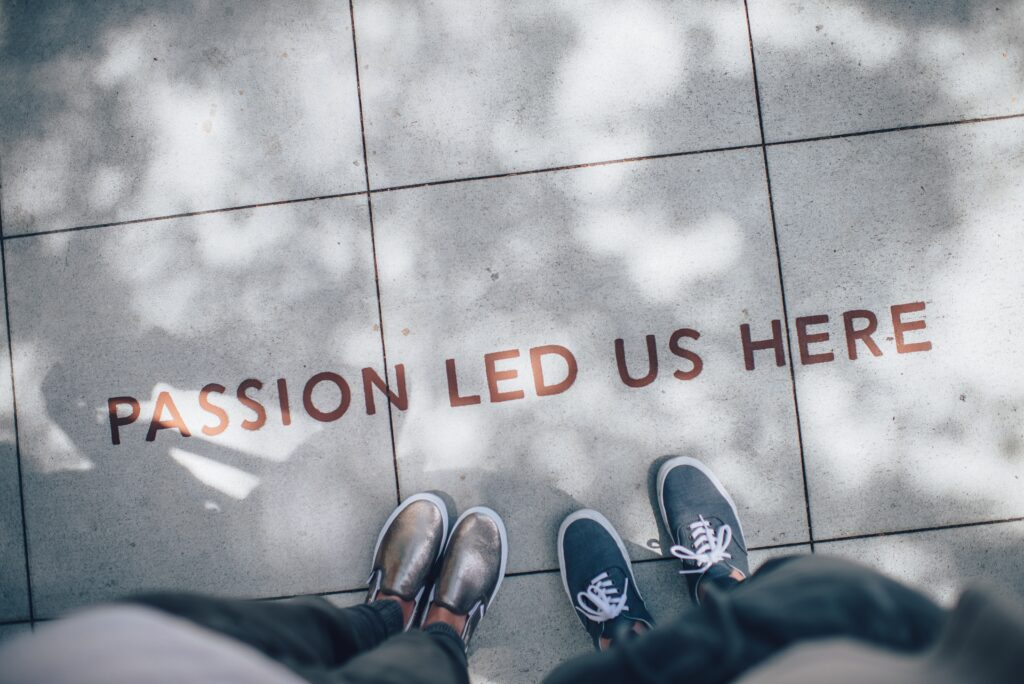 image with two people standing and the words passion let us here